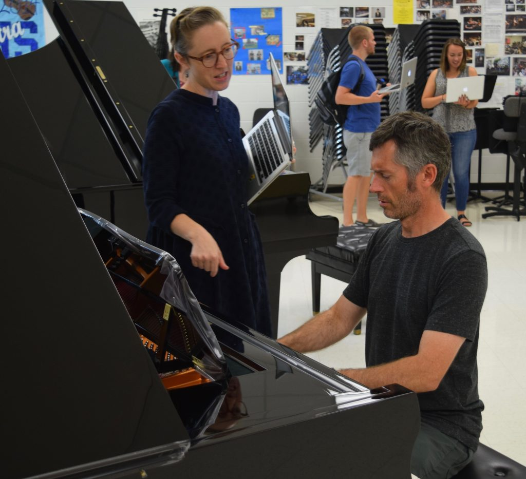 Clague band teacher Jay Macarthur plays the piano while another music teacher asks him a question