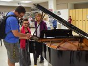 3 AAPS teachers inspect a baby grand piano