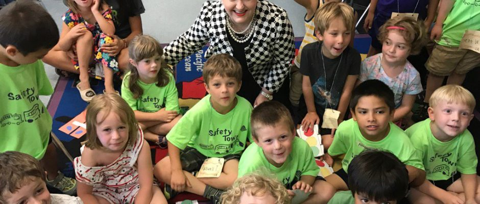 Superintendent Jeanice Swift sits with about a dozen pre-school aged kids in bright shirts