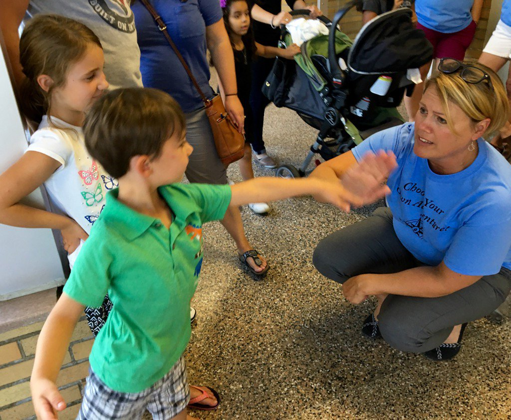 Principal Kerry Beal welcomes two young students to Allen Elementary's temporary home at Ypsilanti's West Middle School.