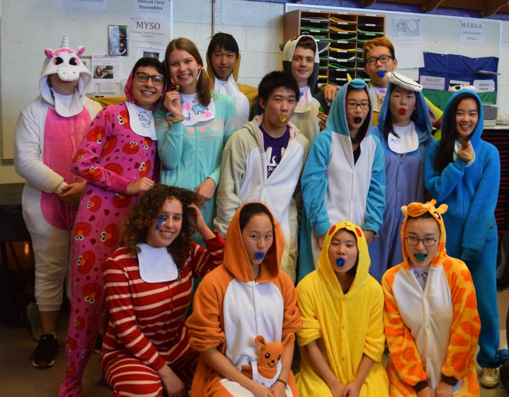 A group of high school students all dressed in colorful pajama style costumes.