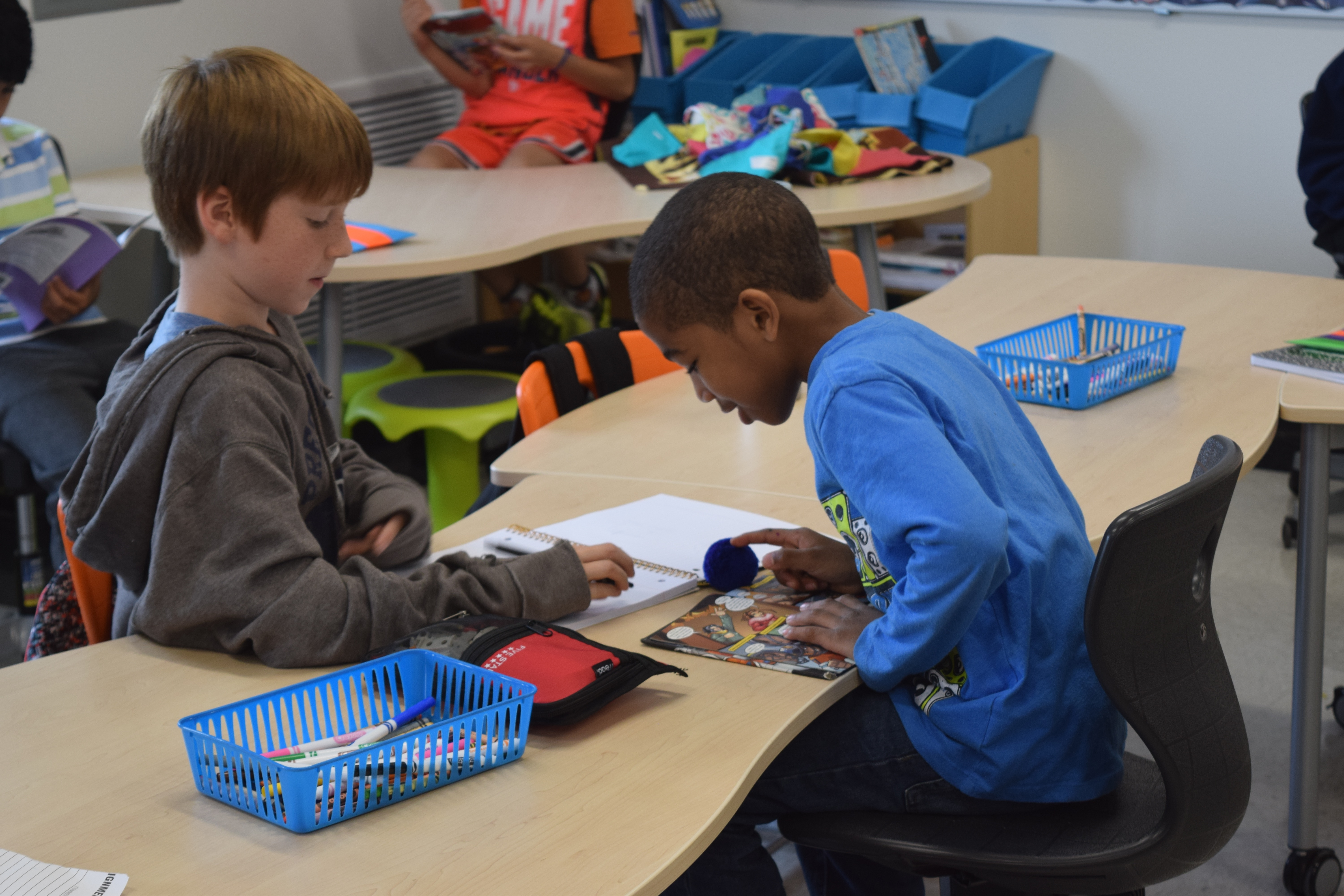 Two 3rd grade students reading across from each other at a desk