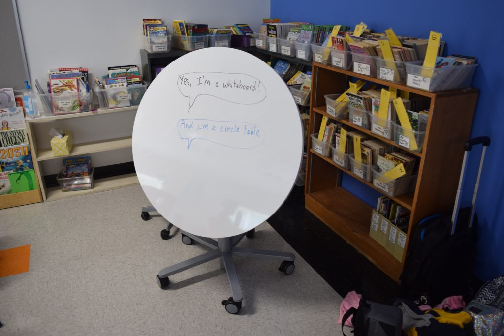 A white flip top table that also serves as a white board.