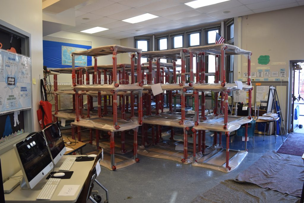 Stacks of tables wait in an Angell Elementary room to be taken to the appropriate classroom.