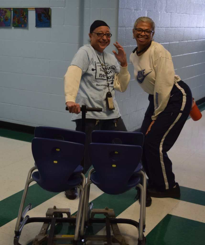 Two custodians at Dicken Elementary smiling behind a cart with four chairs.