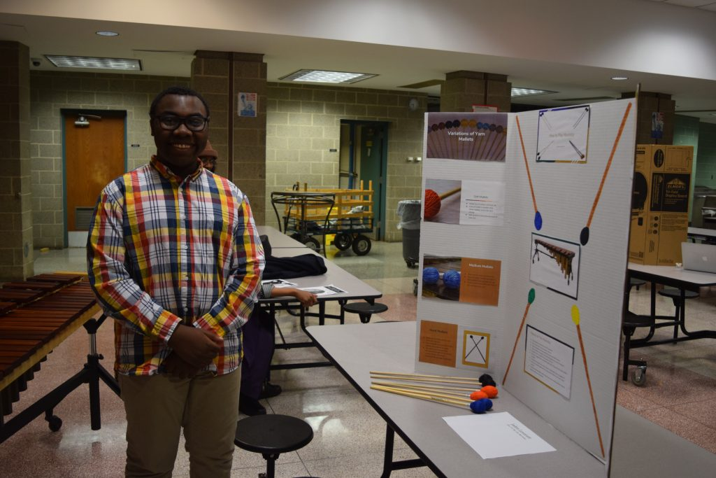 Huron sophomore Jaden Leverett stands next to his project, How to Play the Marimba.