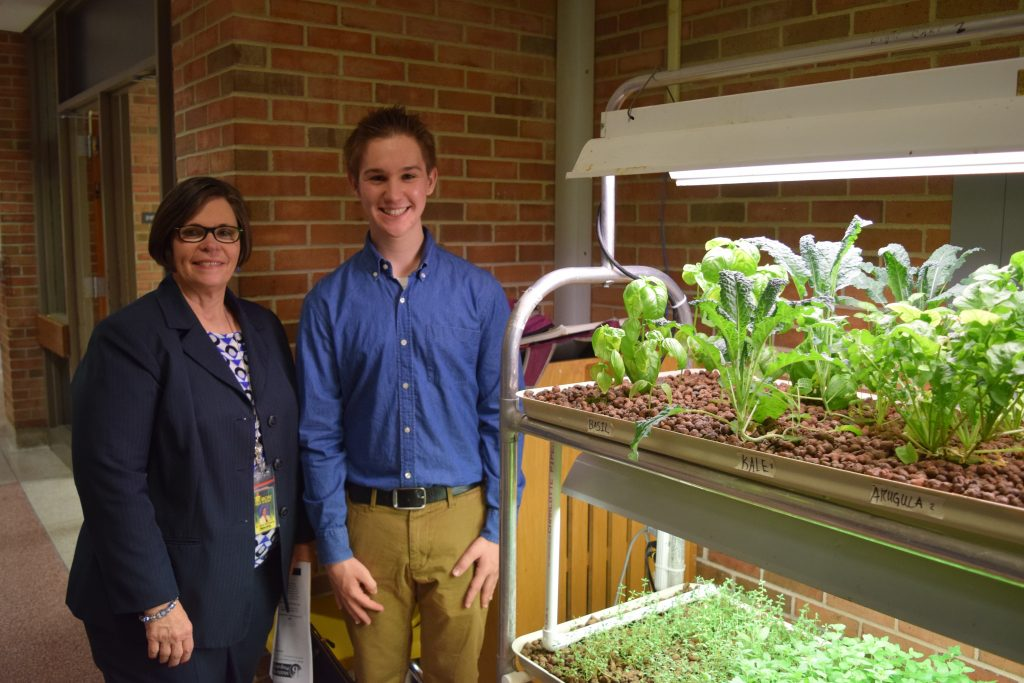 Principal Janet Schwamb and Huron Sophomore Luke Hurley stand next to a variety of greens growing in trays.