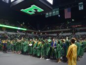 Members of the Huron High School Class of 2018 toss the caps into the air as they celebrate graduation