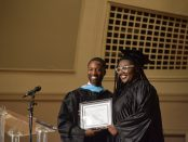 Interim Principal Shaenu Micou in graduation gown handing Alexis Harrison in cap and gown an award.