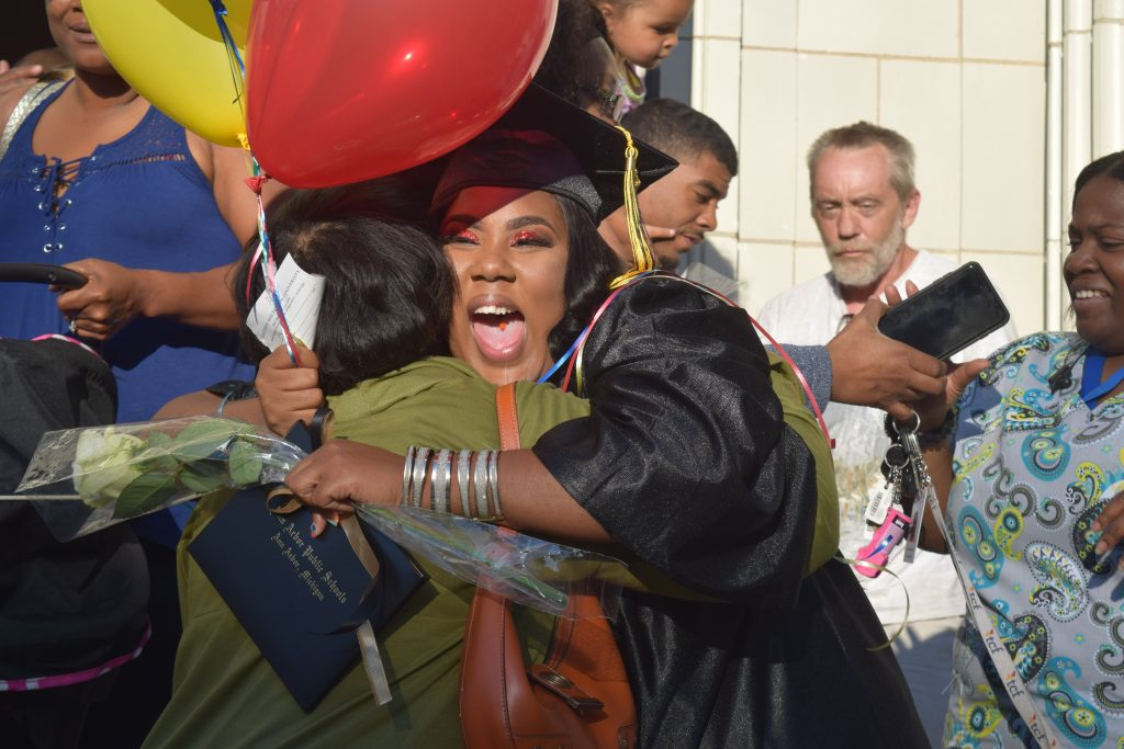 Pathways Class of 2018 graduate hugging a supporter on the steps of Pease Auditorium after the graduation ceremony