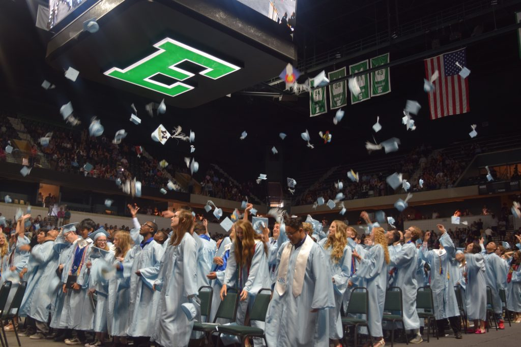 Skyline Graduates celebrate by throwing their caps up into the air