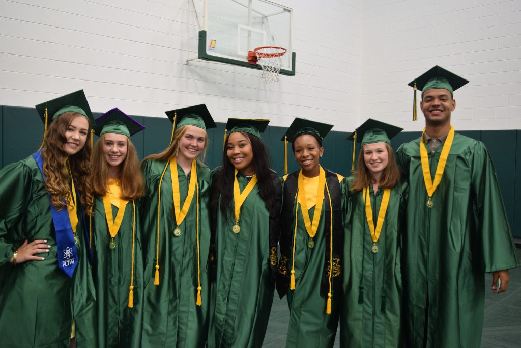 Seven members of the Huron class of 2018 pose in caps and gown before their graduation ceremony.