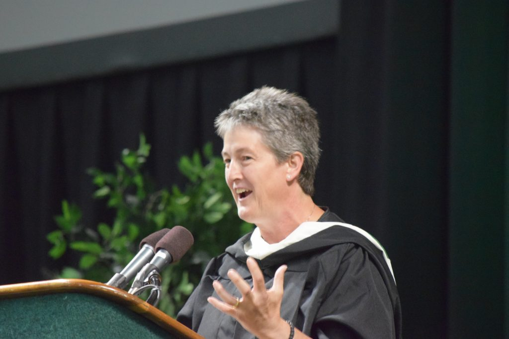 Humanities teacher Amy Van Appledorn speaking at a podium