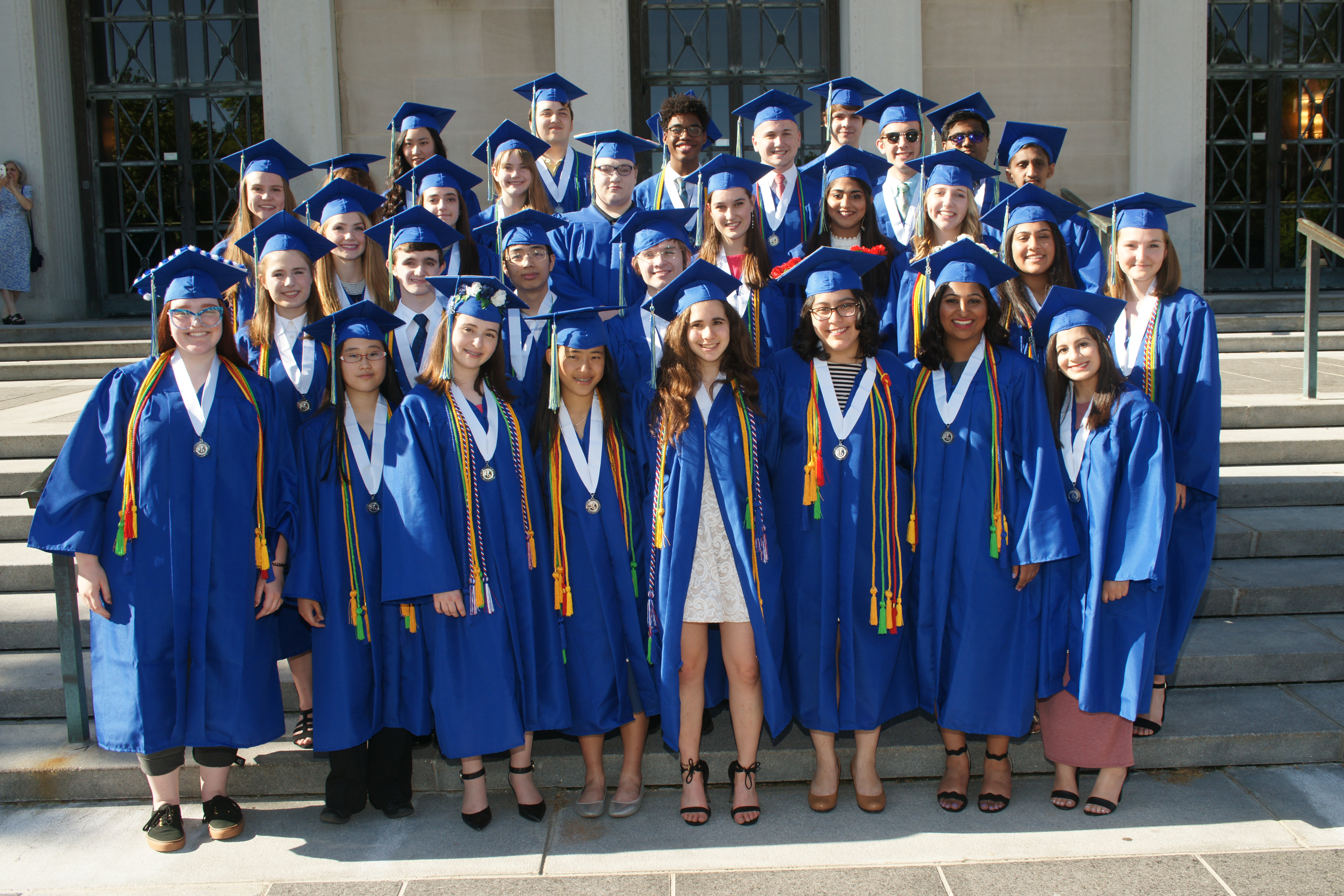 the 31 AAPS graduates in the Washtenaw International High School Class of 2018 stand in front of Rackham Auditorium in their blue caps and gowns