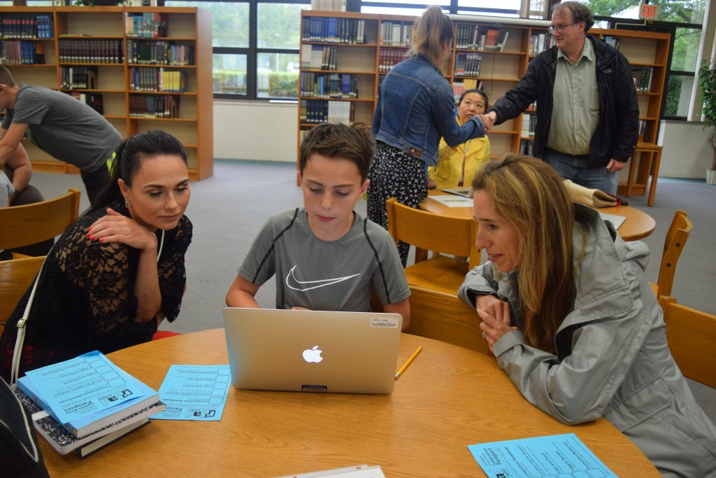 A student shows on a laptop what he learned in ELA Camp to his mother and School Board President Christine Stead