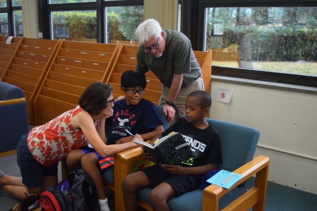 Two parents and a couple of students sitting in the Pioneer Library while one student reads from a boo