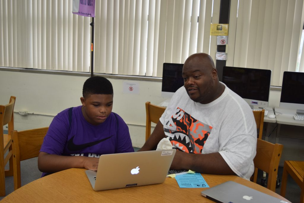 An African-American student and his father look at a laptop as the son explains what he learned in the ELA Camp