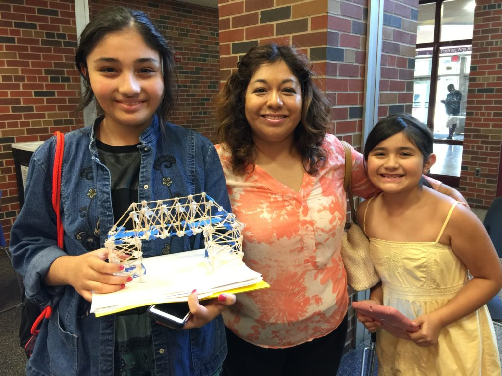 A middle school aged girl holds a toothpick bridge stands next to her mother and younger sister