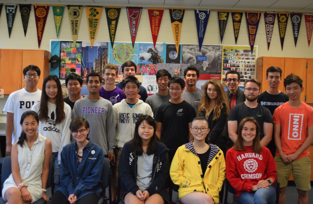 Pioneer High School's 2019 National Merit Semi-Finalists pose in a classroom with lots of college pennants behind them.