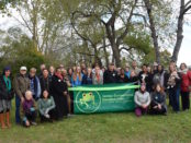 A group of about 50 students, community members, members of the Board of Education, and AAPS teachers and leaders stand behind a ribbon and the Freeman Environmental Education Center's banner.