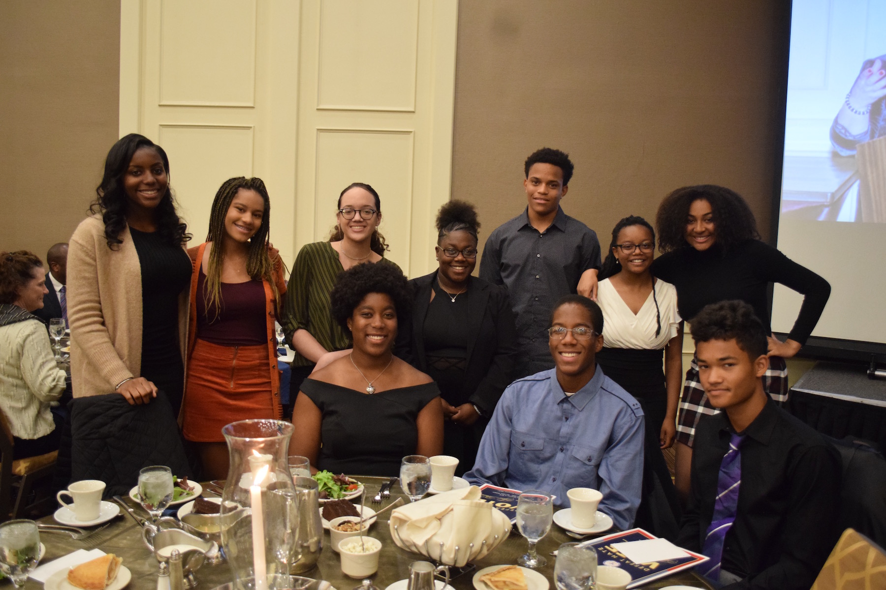 A group of the 2018 Freedom Fund Scholars stand and set at their table