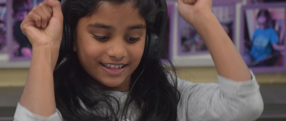 A Lakewood student celebrates as she has a coding success during an Hour of Code event
