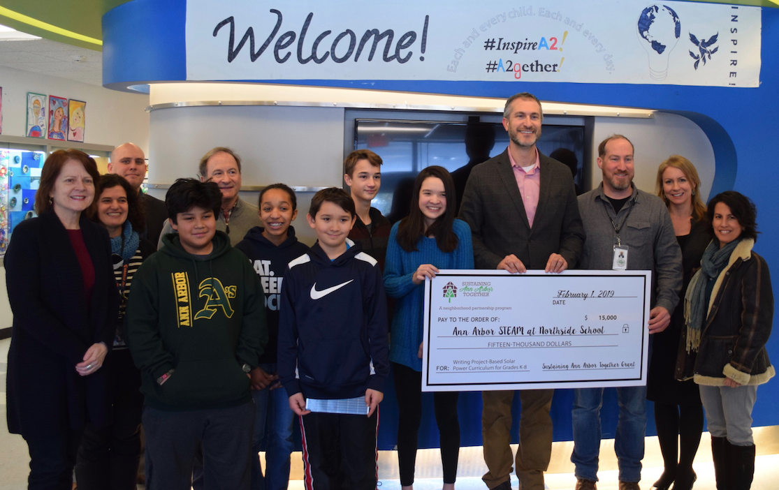 Ann Arbor Mayor Christopher Taylor holds a check while surrounded with A2 STEAM students, staff, as well as Ann Arbor city government officials
