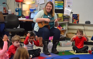 Teacher Amy Sierzega plays a guitar as students sit in a circle around her