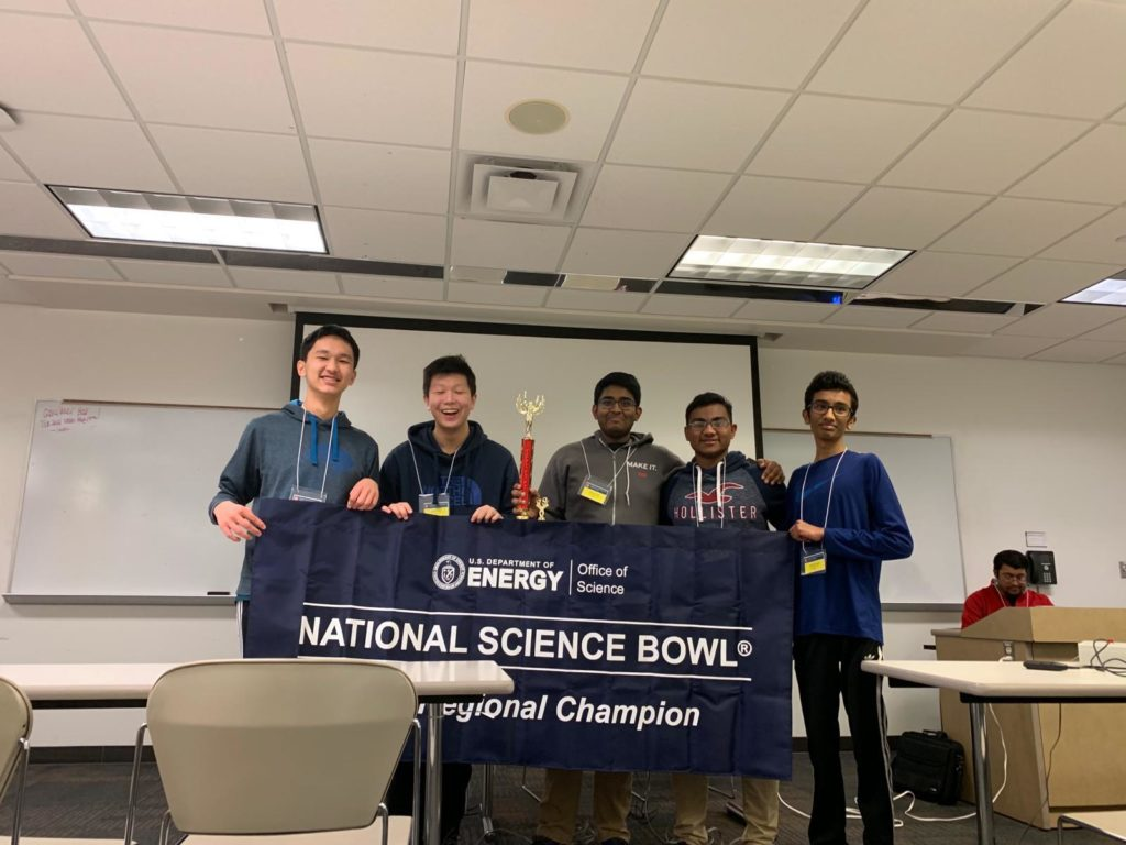 5 members of Huron's science bowl team hold a National Science Bowl banner and their trophy