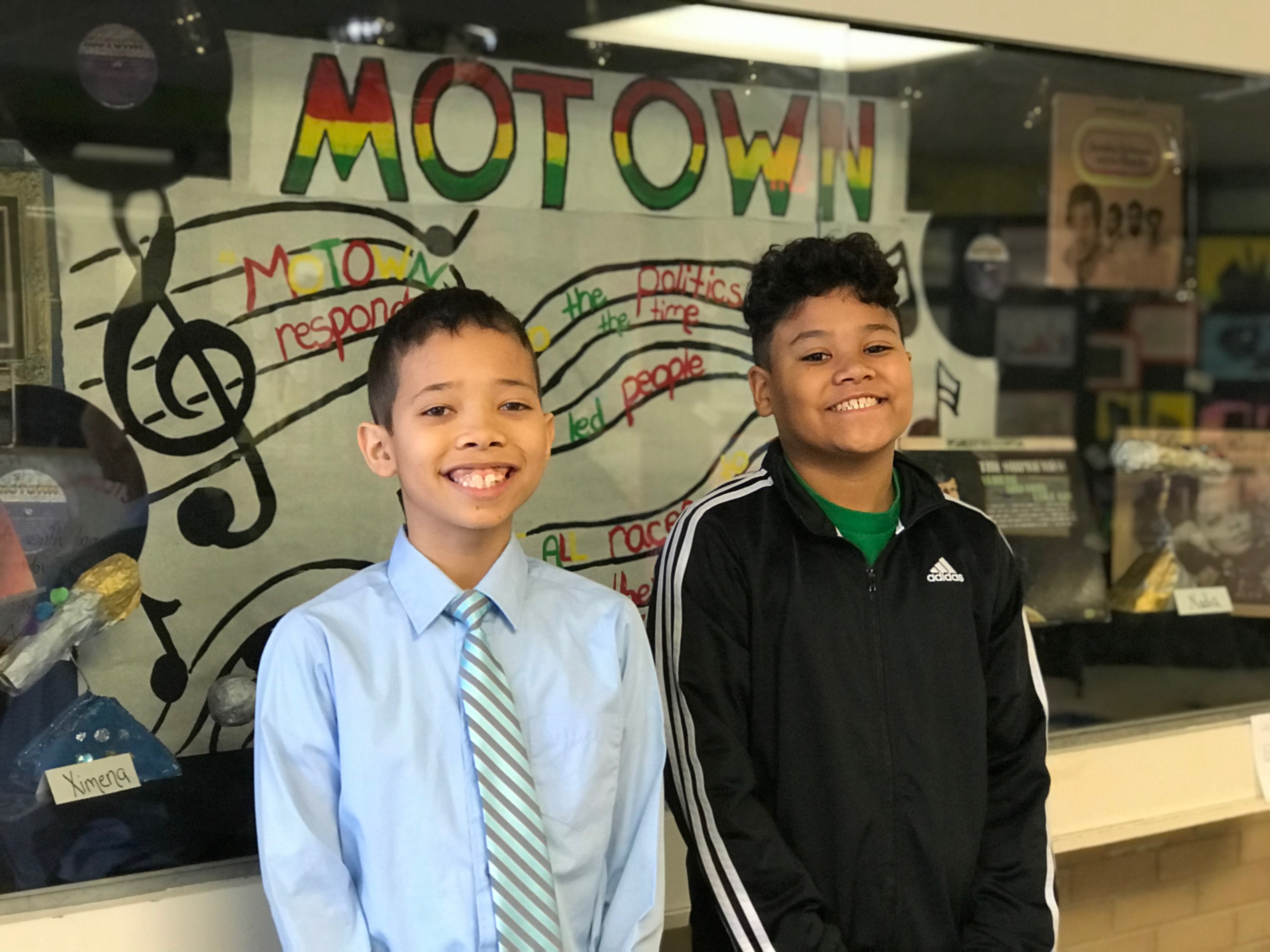 a pair of Mitchell Elementary students stand in front of a sign celebrating Motown music