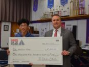 Pioneer 10th grader Brian Khuu holds a giant check for winning the Focus on the Road video competition with the Suburban Collection's Dan Wiebelhaus
