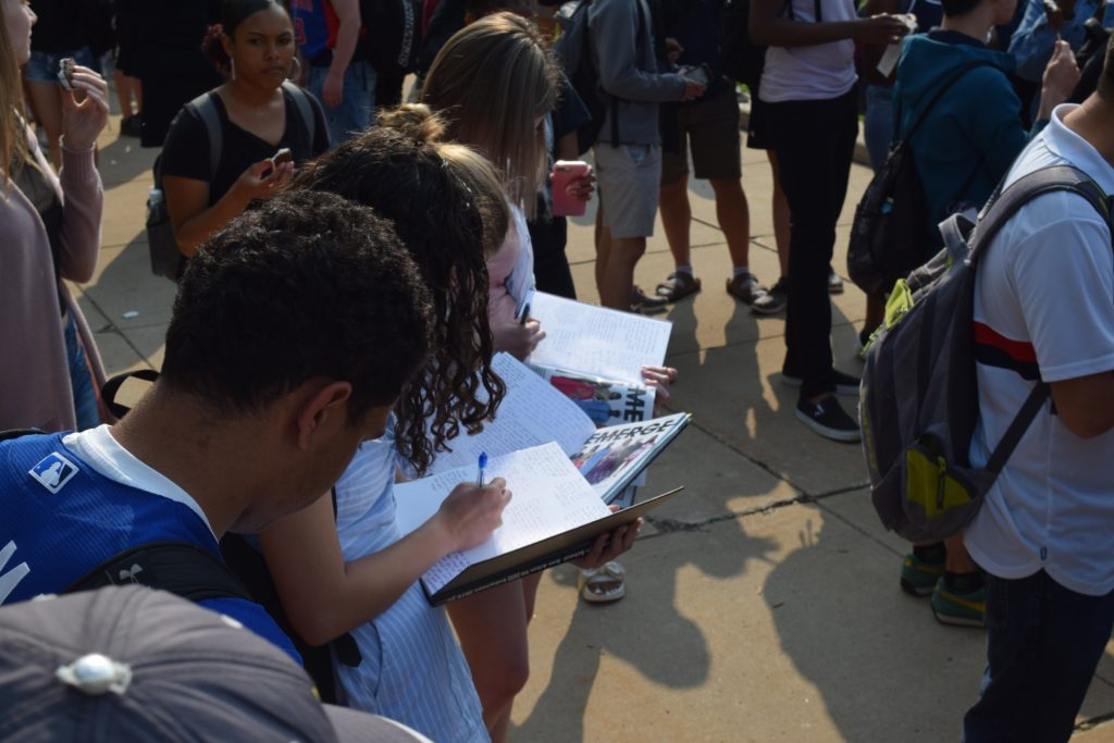 Members of Huron's class of 2019 sign yearbooks after walking out of school for the last time as students.