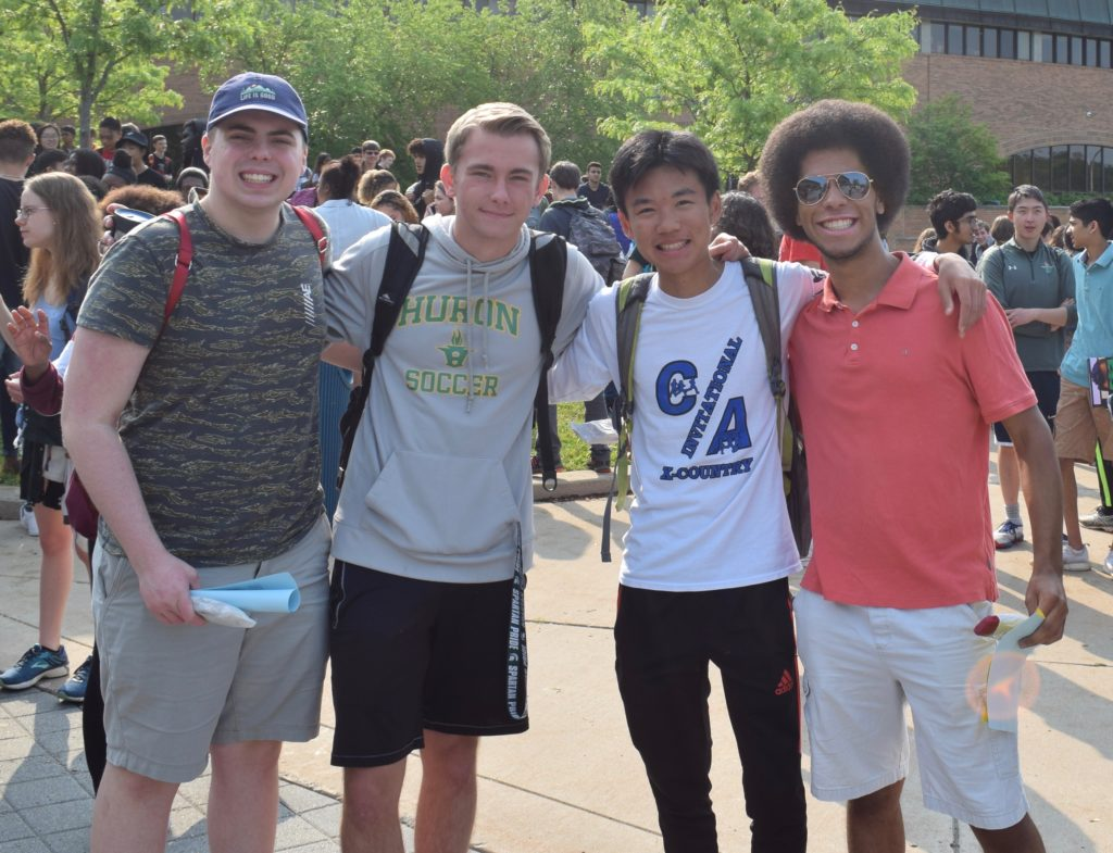 Four male Huron High School students celebrate their last day of school before graduation