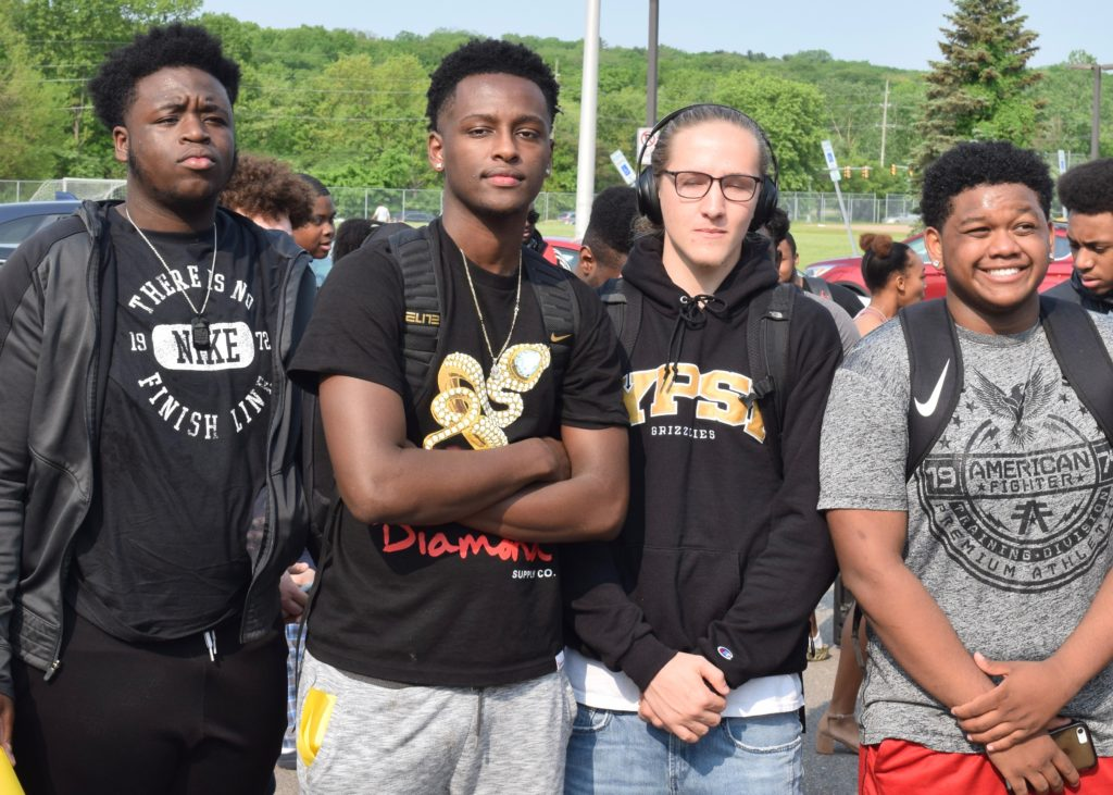 Several male students in Huron's class of 2019 celebrate finishing high school