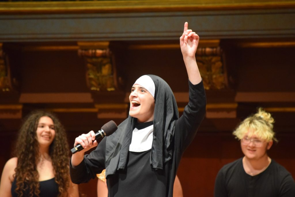 Community student dressed as a nun sings