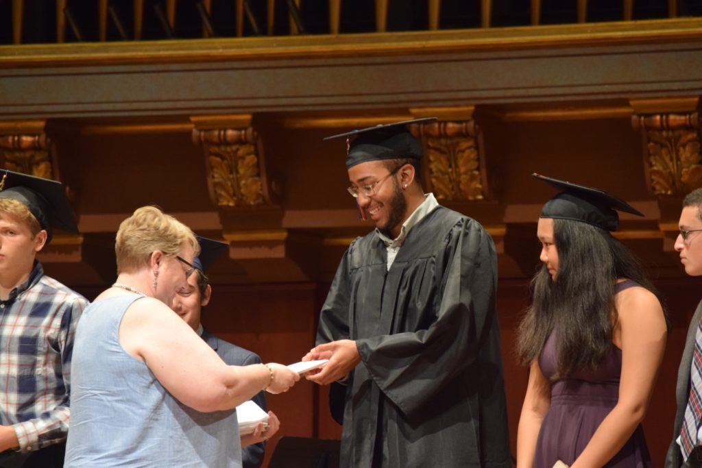 An African American Community graduate receives his diploma.