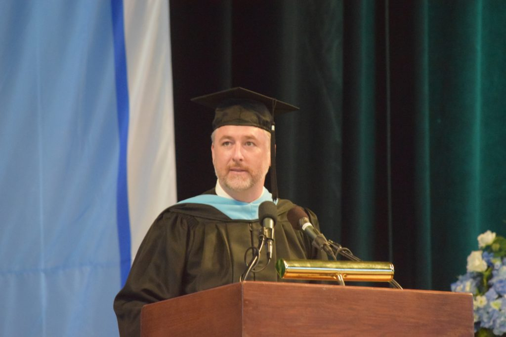 Principal Cory McElmeel in a cap and gown giving the Commencement Address