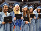5 female members of the Skyline High School class of 2019 holding their diplomas at graduation