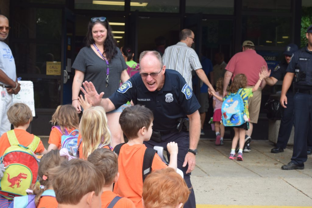 Police officers great Safety Town students with high fives and encouraging words
