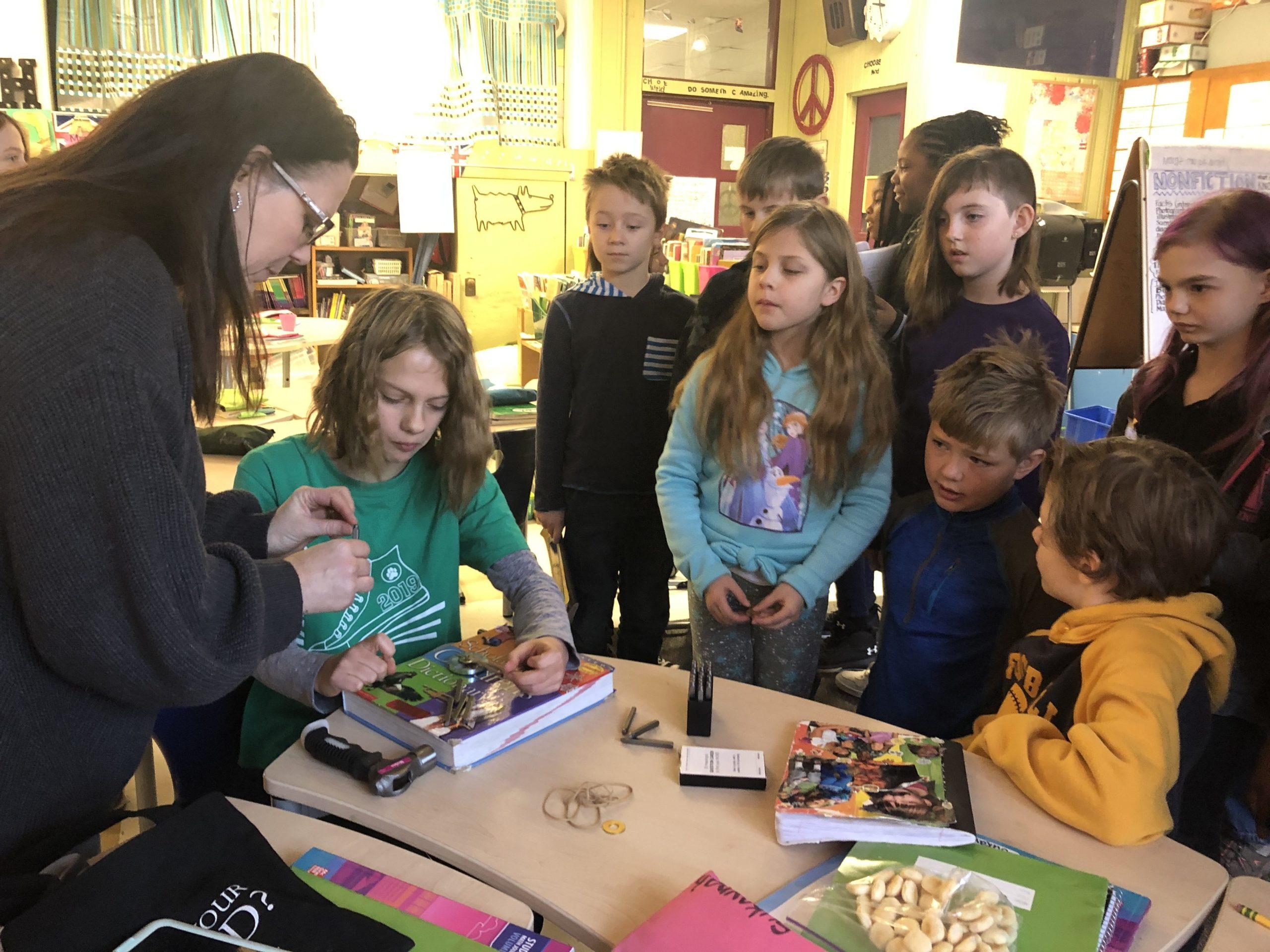 Ellen McGee helps her students emboss their favorite words on a token to wear around their necks.