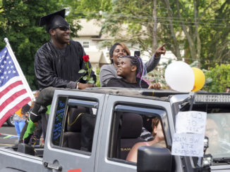 A Pathways graduate stands in the back of a silver jeep with friends and family