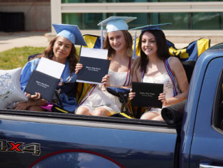 Three female graduates in the Skyline class of 2020 in the back of a pickup truck holding their diplomas