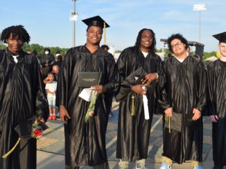 Five members of Pathways class of 2021 in their caps and gowns holding diplomas and smiling
