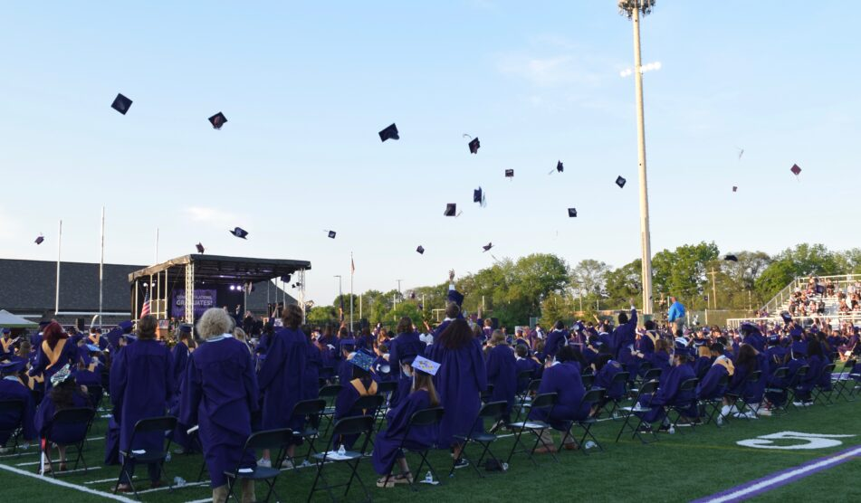 Pioneer Class of 2021 throw their caps into the air